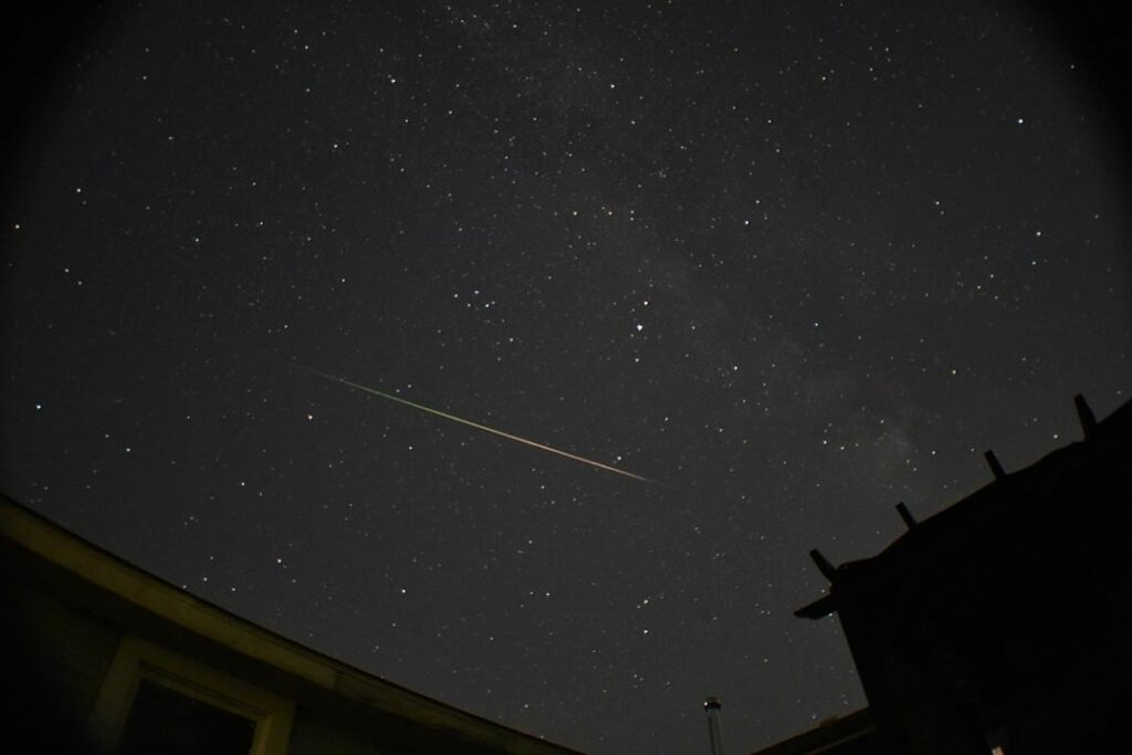 A night sky over a backyard shows a clear meteor shower