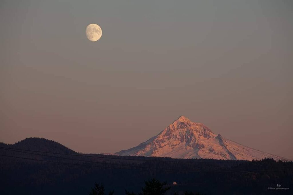 The sun descends and the moon ascends with Mount Hood in the background