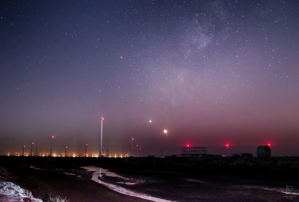 Venus-Moon-Jupiter Trio, Milkyway, Windmill Turbines and their Light, Water and Cold Breeze at Sindh Coastal Highway Wind Corridor.  (Credit: Imran Rasheed Photography)