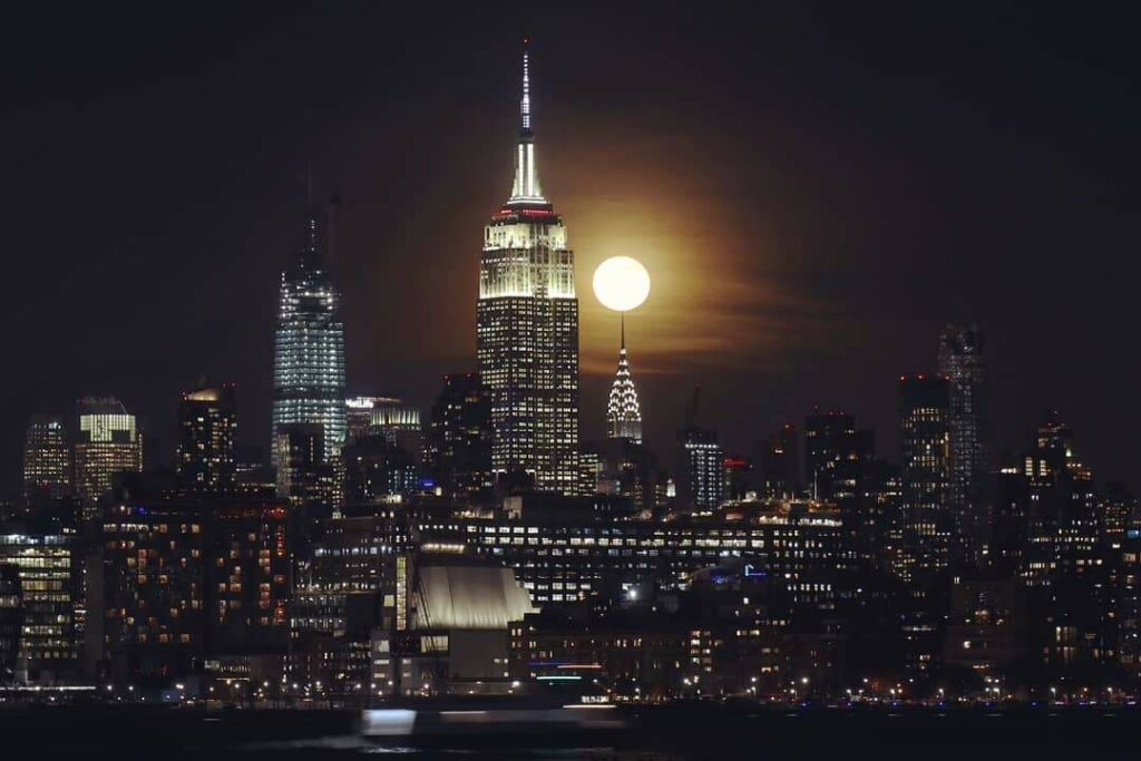 The Cold Moon sits atop the Chrysler Building as it rises next to the Empire State Building in New York City tonight.